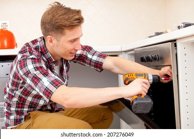 young worker installs a new electric cooker