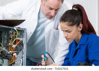 Young worker learning to use soldering iron