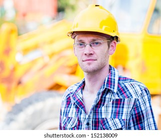 young worker near a yellow bulldozer