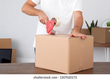 Young worker packing cardboard box in room, closeup. Moving service