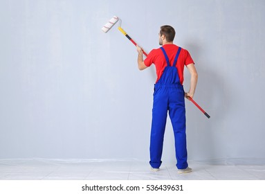 Young worker painting wall in room