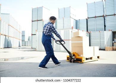 Young worker pushing load cart in front of himself while walking towards storage container