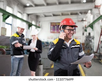 A young worker in a red helmet on the phone. A young worker on the phone discussing the work plan. A man smiles and talks on the phone. In the background as an engineer.