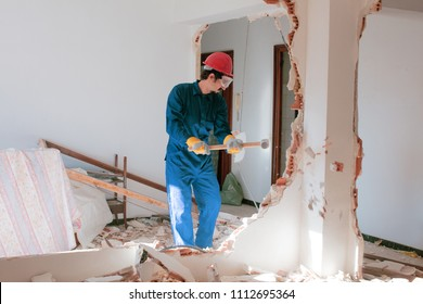 young worker with a red protection helmet and wearing a blue boiler suit. demolition concept