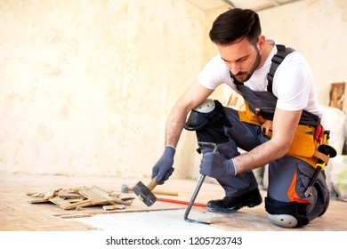 Young worker removing old flooring with adequate removal tolls