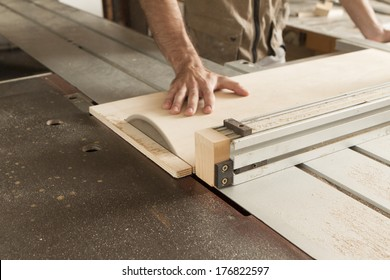 young worker while cutting with circular saw
