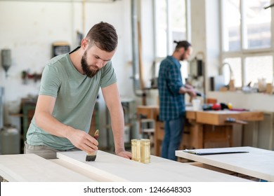 young worker with workpiece in a carpenter's workshop painting wood with brush