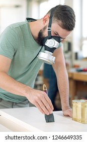 young worker with workpiece in a carpenter's workshop painting wood with brush and respirator