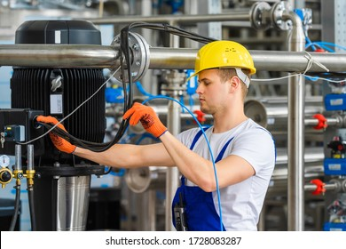 A young worker in a yellow helmet and orange gloves checks the connection of electrical cables at an industrial plant for the treatment of contaminated water. Pipelines and engines in the background.