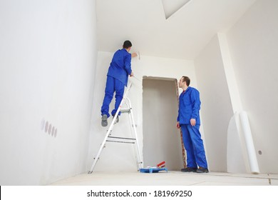 Young workers in blue clothes glue paint fiberglass on ladder in new apartment