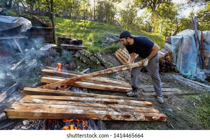 Young workers handling the timber struts. Handsome men treating timber against rotting, by carbonization. Old traditions, rudimentary conservation techniques.