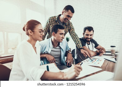Young Workers Have Conversation in Modern Office. Brainstorm at Work. Smiling Woman. Man on Wheelchair. Smiling Manager. Teamwork in Office. Young Worker. Sitting Man. Communication with Colleagues.