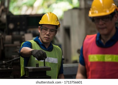 Young workers are improving steel lathes in the factory.