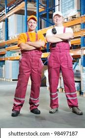 young workers men in uniform in front of warehouse rack arrangement stillages