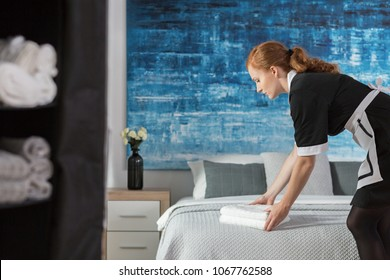 A young, working maid laying fresh, white towels on a bed in a hotel room