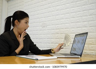 Young working woman get more money from business online. Professional smart young woman using a laptop building online business making money dollar bills cash coming out of computer.