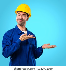 Young workman with helmet extending hands to the side and smiling for presenting and inviting to come on blue background