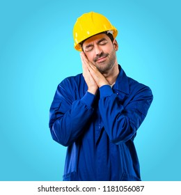Young workman with helmet making sleep gesture. Adorable and sweet expression on blue background