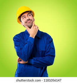 Young workman with helmet standing and thinking an idea on green background