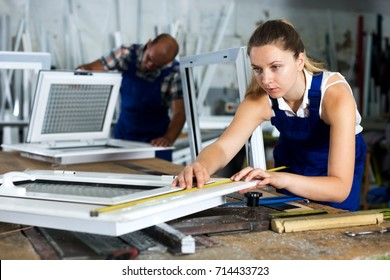 Young workwoman controlling size of finished PVC window with measuring tape in workshop