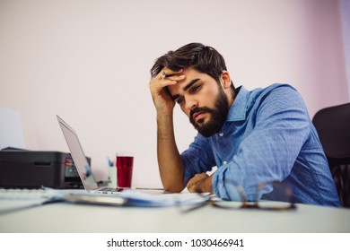 Young worried businessman holding his head.