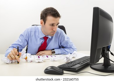 Young worried confused business man looking at data on computer display and holding a pencil in his hand with crumpled paper sheets on desk.
