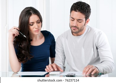 Young worried couple looking at their bills and home finance at home