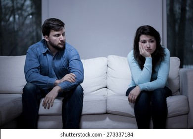 Young worried couple sitting on the couch