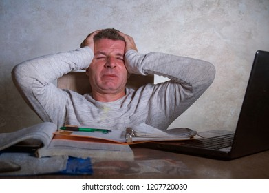 young worried and desperate man working late night at home desk with laptop computer feeling frustrated and tired accounting paperwork or studying for exam isolated suffering anxiety crisis