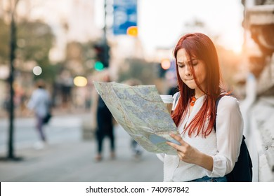Young worried female traveler lost in the city using map