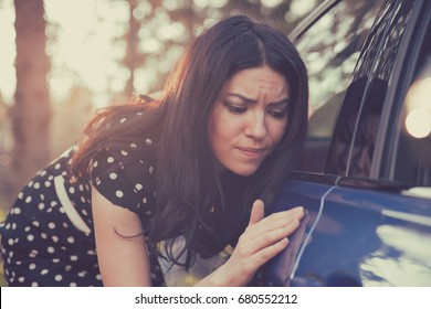 Young worried funny looking woman obsessing about cleanliness of her new car. Automobile care and protection concept