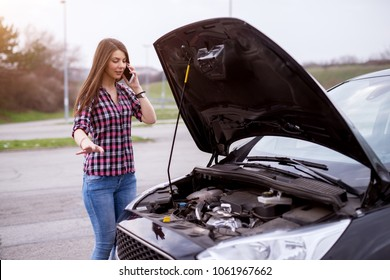 Young worried girl is using a phone to explain the mechanic the problem with a car that she has.
