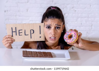 Young worried latin woman feeling tempted and guilty wanting to eat chocolate and donuts asking for help in diet calories sugar addiction nutrition and lifestyle concept.