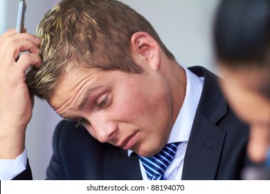 Young worried and stressed businessman scratch his head