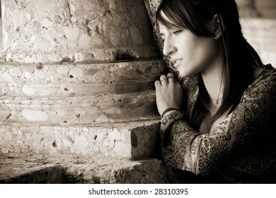Young worried woman against old stone column