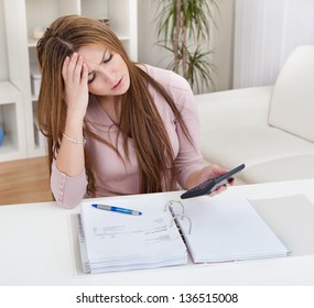 Young Worried Woman Calculating Bills At Home