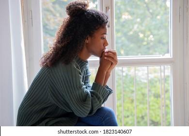Junge besorgte Frau, die aus dem Fenster schaut