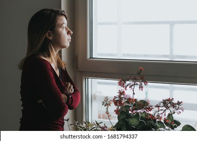 Young worried woman looking through the window