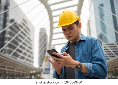 Young worry foreman engineer worker with yellow helmet using smartphone or mobile phone to check construction project plan ordered by construction site manager in Bangkok city. Industrial concept