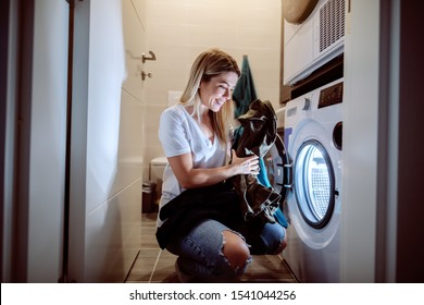 Young worthy caucasian blonde smiling housewife crouching and putting laundry in washing machine. Bathroom interior, night work concept.