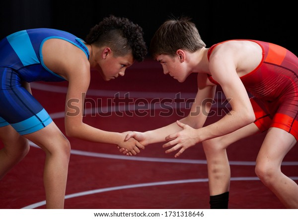 Young wrestlers shaking hands at the start of a match showing good sportsmanship