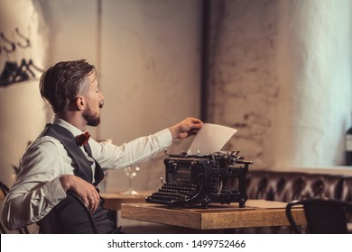 Young writer with a retro typewriter in a restaurant