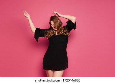 Young xxxl woman, happy plus size model girl in short black dress dancing at the pink background, isolated. Copy space