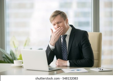 Young yawning businessman working with laptop at desk in the modern office, unmotivated employee, not completing job duties, do not have the drive to succeed, dissatisfaction in office environment
