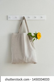 Young Yellow Sunflower in Textile Eco Bag Hanging on Hook Isolated on White Wall Background Copy Space. Blank Canvas Recycle Reusable Shopping Sack. Natural Organic Material Packaging