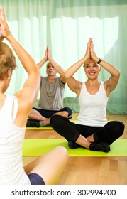 Young  yoga instructor showing asana to senior attenders