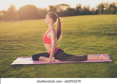 Young yoga trainer is making stretching outdoors in spring park on a nice green grass, so relaxed and healthy, wearing modern pink and black sport outfit, with tail