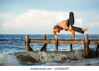 Young yoga trainer practicing yoga dandasana pose on a wooden pier on a sea or river shore. Healthy lifestyle concept