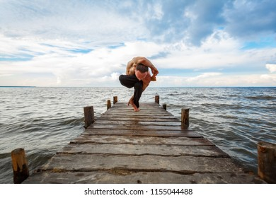 Young yoga trainer practicing yoga exercises on a wooden pier on a sea or river shore with a scenic view. Healthy lifestyle concept