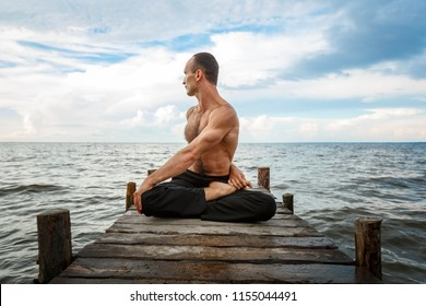 Young yoga trainer practicing yoga exercises on a wooden pier on a sea or river shore.Healthy lifestyle concept